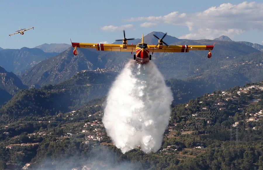 Противопожарный самолет-амфибия Canadair выливает воду на очаги возгорания в лесу Карро, недалеко от Ниццы, Франция, 24 июля, 2017 года.