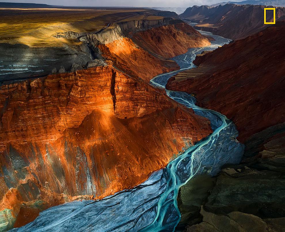 Солнечный свет отражается от минеральных пластов разных цветов в Гранд-Каньоне Душанзи, Китай.