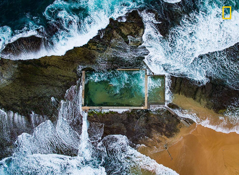 В Сиднее, Тихий океан во время отлива обнажает природный утес. Избегая толпы на многих пляжах города, местные плавают в этом бассейне.