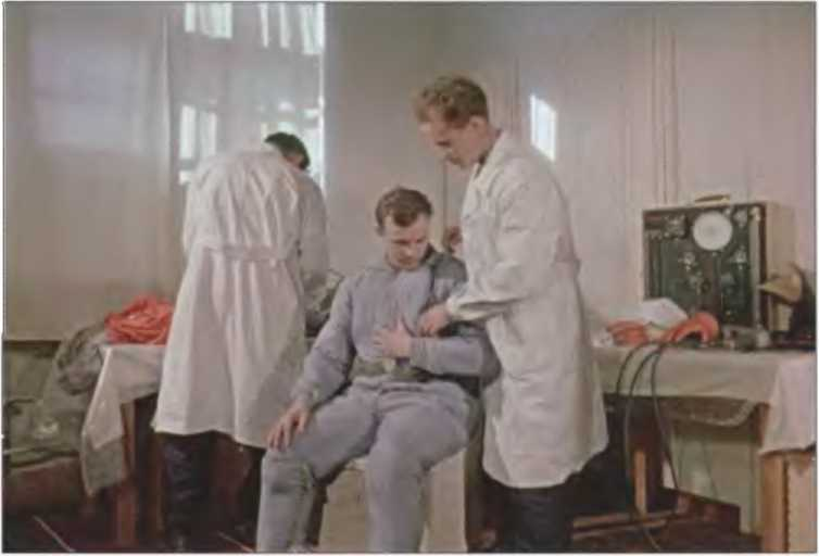 Гагарин Ю. А. во время надевания скафандра. Справа В. И. Сверщек, 12 апреля 1961 г