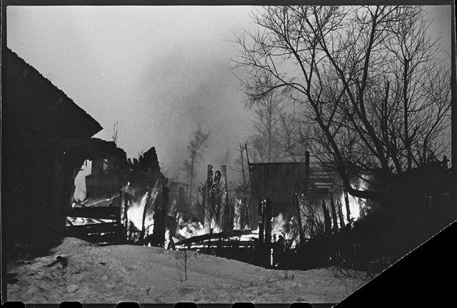 На путях отступления немцев в районе Гатчины горят подожженные гитлеровцами дома на Красной улице, переименованной немцами в Штутгартштрассе. Ленинградский фронт, 1943 год: